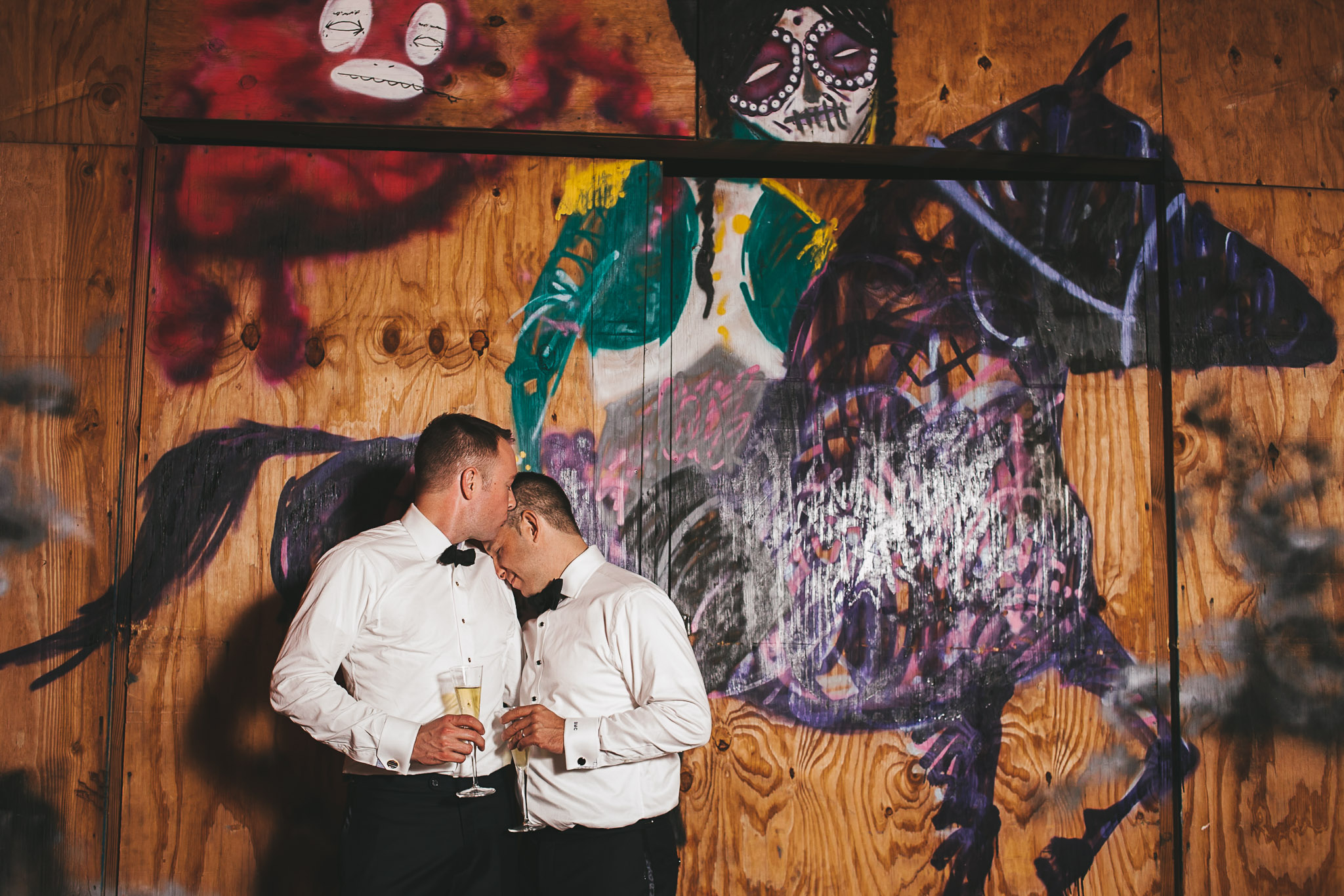 Brooklyn Wedding Photographer, Two Grooms in front of a colorful graffiti mural